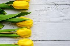 Gelbe Tulpenblumen auf weißem hölzernem Hintergrund Wartefrühling Glücklicher Muttertag, am 8. März Flache Position, Draufsicht p stockbild