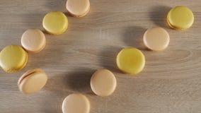Gelbe und beige Makronen auf h?lzernem Hintergrund, Rollen mit einen Pl?tzchen ?ber der Tabelle stock footage