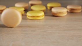 Gelbe und beige Makronen auf h?lzernem Hintergrund, Rollen mit einen Pl?tzchen ?ber der Tabelle stock video footage