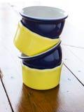 Gelbe und blaue Ramekins gestapelt auf Holztisch Lizenzfreies Stockfoto