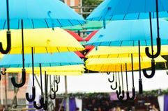 Gelbe und blaue und rote Regenschirme unter dem schönen bewölkten Himmel farbe Lizenzfreie Stockfotografie