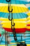 Gelbe und blaue und rote Regenschirme unter dem schönen bewölkten Himmel farbe Stockfotos