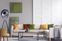 Gelbe und grüne Kissen auf weißem Sofa im Wohnzimmerinnenraum mit Malereien und Lampe Reales Foto lizenzfreie stockbilder