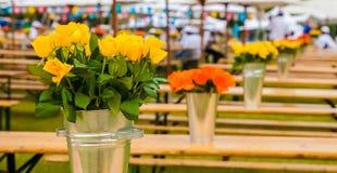Gelbe und orange Blumen auf Picknick setzt unter Regenschirmen auf die Bank stockfotos