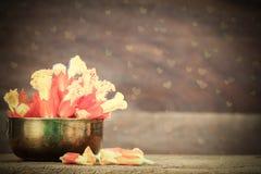 Gelbe und orange Blumen in der Schmutzmessingschüssel mit Herzen formten bokeh auf unscharfem hölzernem Hintergrund Stockfoto