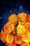 Gelbe und orange Rosen über blauem Hintergrund Stockbilder