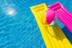 Gelbe und rosa Luftmatraze mit aufblasbarem Ball auf Schwimmbad Lizenzfreies Stockfoto