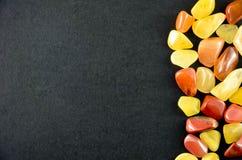 Gelbe und rote Steine auf schwarzem bakground Lizenzfreie Stockfotos