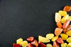 Gelbe und rote Steine auf schwarzem bakground Lizenzfreies Stockfoto