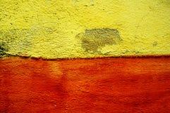 Gelbe und rote Zement-Wand Lizenzfreie Stockfotos