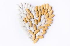 Gelbe und weiße Vitamine in den Pillen auf einem weißen Hintergrund lizenzfreie stockfotos