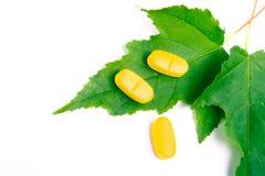 Gelbe Vitaminpillen über grünen Blättern Lizenzfreies Stockfoto