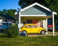Gelbe Volkswagon-Wanze vor amerikanischer Flagge lizenzfreie stockfotos