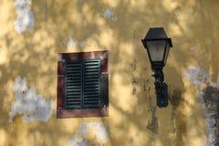 Gelbe Wand mit Fensterfensterladen und -lampe Lizenzfreies Stockbild