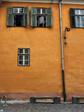 Gelbe Wand mit grünen Fenstern Sibiu Rumänien Stockbilder