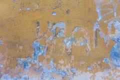 Gelbe Wand mit Sprüngen und Schalenfarbe im Schmutz Lizenzfreie Stockfotos