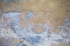 Gelbe Wand mit Sprüngen und Schalenfarbe im Schmutz Stockfotografie