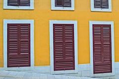 Gelbe Wand mit Türen Stockfoto