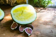Gelbe Wassermelone ohne Knochen und rote Feigen auf einem hölzernen backgro lizenzfreie stockbilder