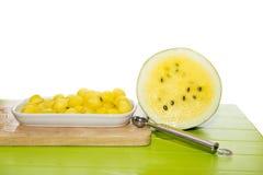 Gelbe Wassermelonenhälfte und der Ball gesetzt auf eine weiße Platte Stockbild
