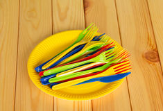 Gelbe Wegwerfplatten mit farbigen Plastikmessern, Gabeln Lizenzfreies Stockbild