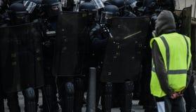 Gelbe Westen - Gilets-jaunes Proteste - Protestierender, der allein vor Bereitschaftspolizei steht stockbild