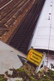 Gelbe Zeichenwarnung für Hochspannungskontaktdrähte über den Schienen und weißer Geschwindigkeitszug im Hintergrund Stockfotos