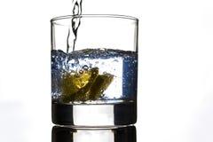 Gelbe Zitrone der Scheibe im Glas Wasser, Bewegungsaktion lizenzfreie stockfotografie