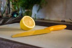 Gelbe Zitrone, die auf ein weißes Schneidebrett nahe bei einem gelben Messer legt Stockbild