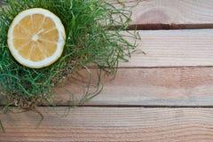 Gelbe Zitrone im Gras auf einem hölzernen Hintergrund Stockfotos