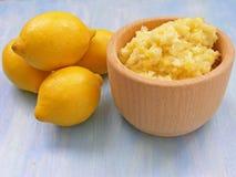 Gelbe Zitronen auf einem schäbigen hölzernen Hintergrund mit Püree von Zitronen im Topf Stockfotos