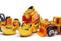 Gelben Spielzeugschwermaschinen mit chinesischem Gold-sycee oder yuanbao Bootsbarren mit Text auf Spitzendurchschnittvermögen, W stockbild