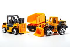 Gelben Spielzeugschwermaschinen schließen Kipplaster, Planierraupe und Gabelstapler auf weißem Hintergrund mit ein lizenzfreies stockfoto