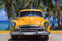 Gelber amerikanischer Oldtimer parkt unter Palmen am pasemko w Varadero Kuba, Seria Kuba 2016 reportażu - Zdjęcie Stock