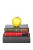 Gelber Apfel auf alten Büchern Stockbilder