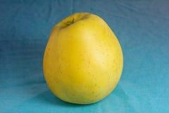 Gelber Apfel auf Blau Lizenzfreie Stockbilder