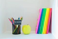 Gelber Apfel, Bleistifte im Halter und multi farbige Bücher Lizenzfreies Stockbild