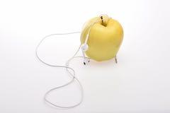 Gelber Apfel und Kopfhörer Stockbilder