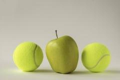 Gelber Apfel zwischen zwei Tennisbällen Stockfotos