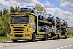 Gelber Autotransporter Scanias R500 schleppt Neuwagen Stockbilder