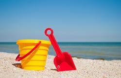 Gelber Babyeimer mit roter Plastikspachtel des roten Spielzeugspielzeugs auf dem links gegen den sonnigen Tag des blauen Seemeers Lizenzfreie Stockbilder