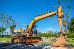 Gelber Bagger gegen Baustelle lizenzfreies stockbild
