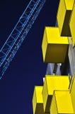 Gelber Balkon und blauer Kran Stockfotografie