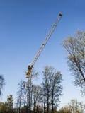 Gelber BauTurmkran und grüne Bäume gegen blauen Himmel Stockbilder