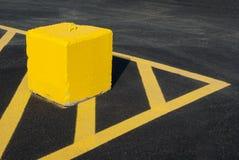 Gelber Betonblock, der Linien Asphalt zeigt Lizenzfreies Stockbild