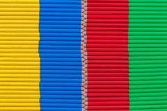 Gelber, blauer, roter und grüner Hintergrund bestanden aus kleinen Bleistiften Lizenzfreies Stockfoto