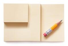 Gelber Bleistift auf dem Notizblock lokalisiert Lizenzfreie Stockfotografie