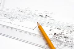 Gelber Bleistift auf der Zeile und Zeichnungen auf dem Tabulator Stockbild
