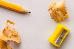 Gelber Bleistift, Bleistiftspitzer und Schnitzel auf Weißbuchhintergrund mit Kopienraum Stockbild