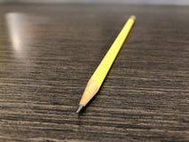 Gelber Bleistift mit dem spitzen Granit, der auf schwarzem kopiertem Schreibtisch nach au?en liegen zeigt stockfotografie